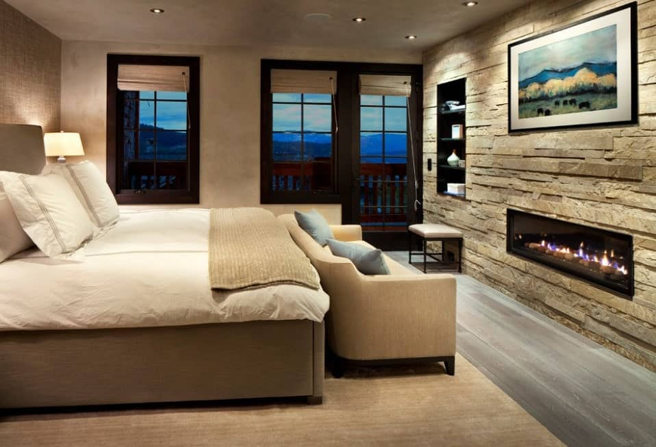 Primary bedroom featuring a stunning wall with built-in shelving and a fireplace. The room features hardwood flooring topped by a classy rug where the large bed and a comfy couch are set.