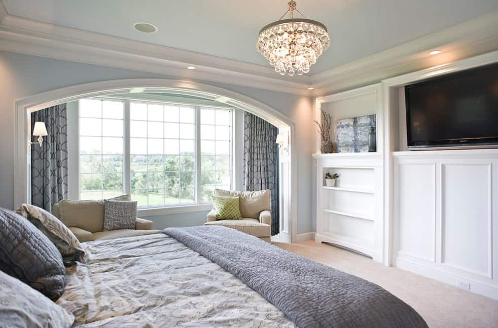 Primary bedroom with blueish gray walls and ceiling lighted by a glamorous chandelier. The room offers a large bed and a widescreen TV on the wall.