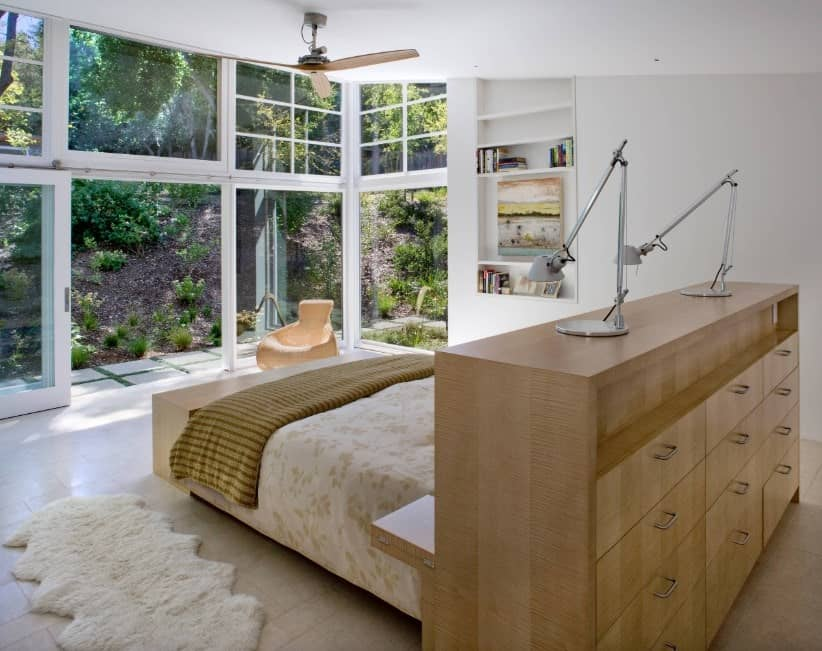 Primary bedroom featuring white walls and glass doors and windows overlooking the beautiful garden area. The bed frame boasts built-in shelving and cabinetry.