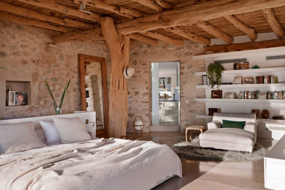 Primary bedroom featuring a rustic ceiling and tiles flooring, along with a large bed and white shelving.