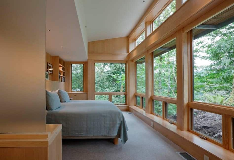This primary bedroom features gray carpet flooring and a large bed. There are multiple glass windows overlooking the peaceful surroundings.