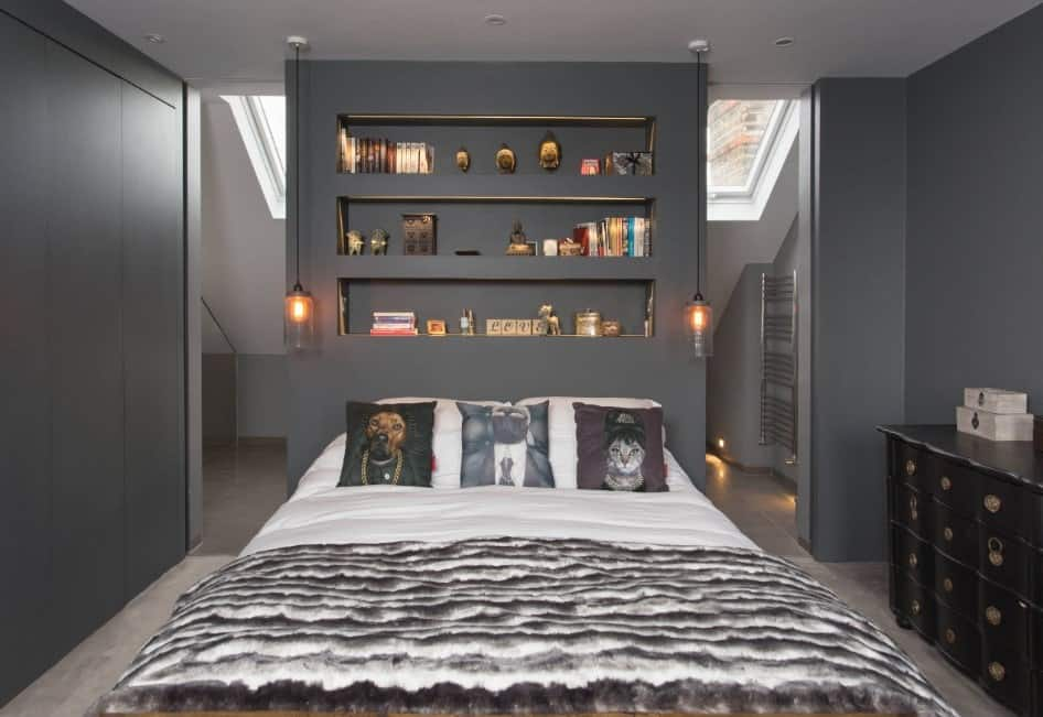 Contemporary primary bedroom with gray walls and a black side table, along with a stylish bed set on the gray carpet flooring.