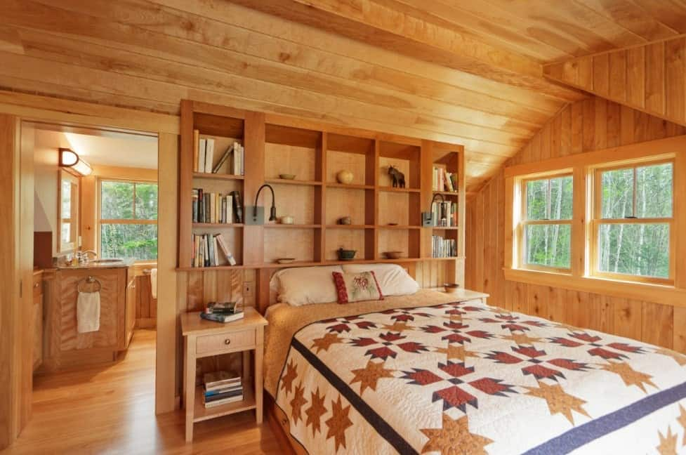 Rustic primary bedroom surrounded by wooden walls, ceiling and floors. The bed frame and the built-in shelves, along with the side tables are all made of wood.