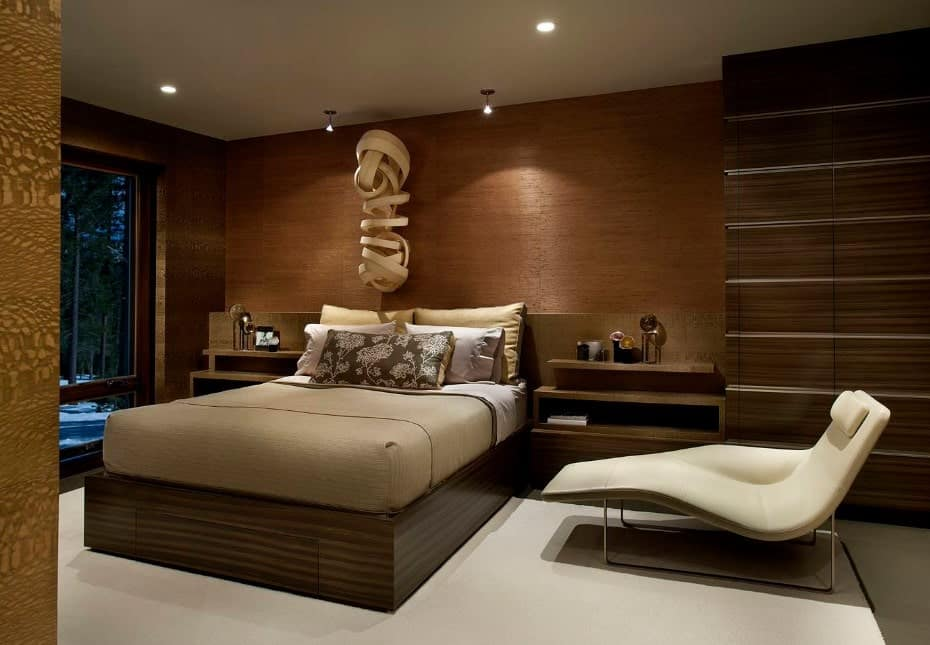 Modern master bedroom featuring a stylish wooden wall and a modish bed with two side tables with built-in shelves. The wall decor is absolutely charming as well.