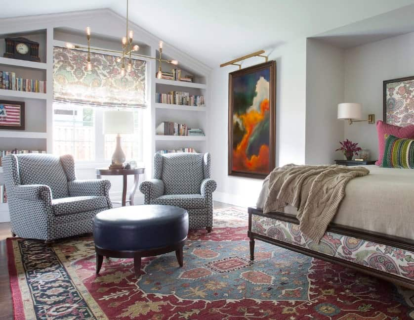Primary bedroom featuring a nice sitting area with two charming chairs and an ottoman set on the large rug covering the hardwood flooring. The room is lighted by elegant ceiling lights.