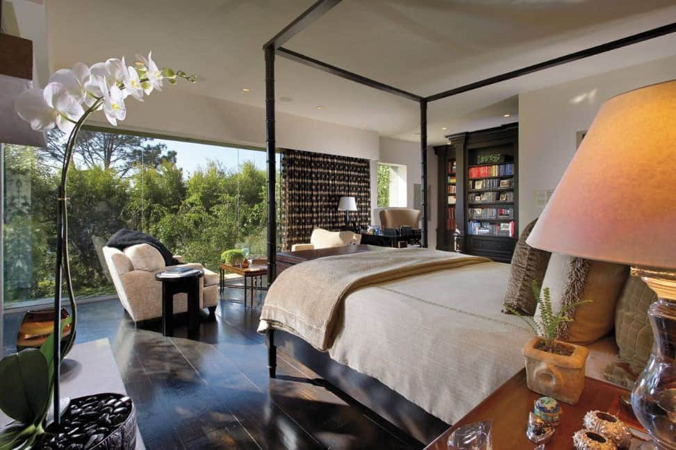 Large master bedroom featuring hardwood flooring and a sitting area, along with a glass wall overlooking the serene outdoor views.