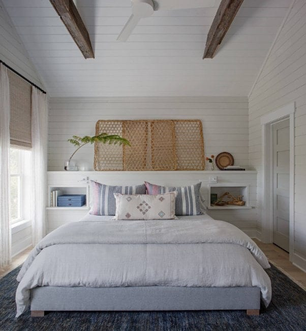 Primary bedroom featuring a large gray rug and a comfy bed. The white walls match the white ceiling with rustic beams.