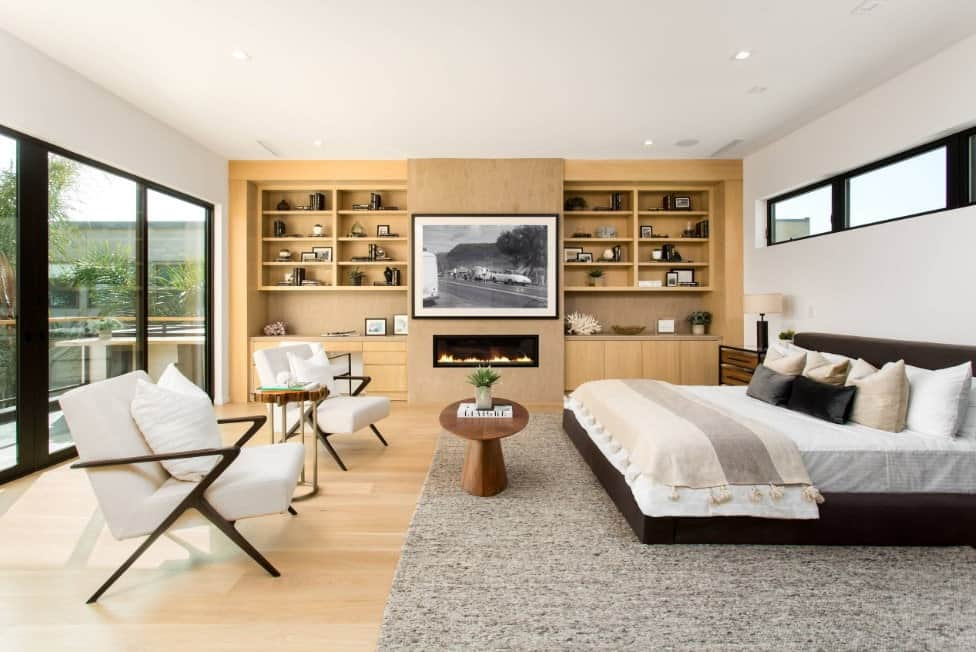 This primary bedroom boasts a large bed set on the gray rug and has a fireplace with attractive wall decor on top. There are bookshelves on both sides of the fireplace.