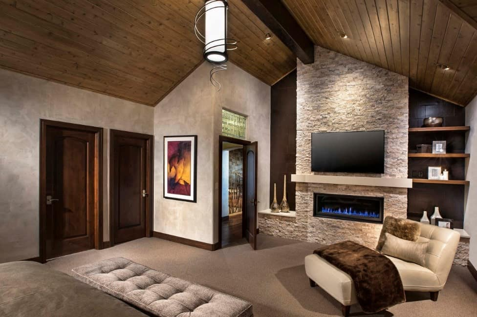Primary bedroom with a gas fireplace and a large widescreen TV on the wall. The room also features carpet flooring and a rustic ceiling.