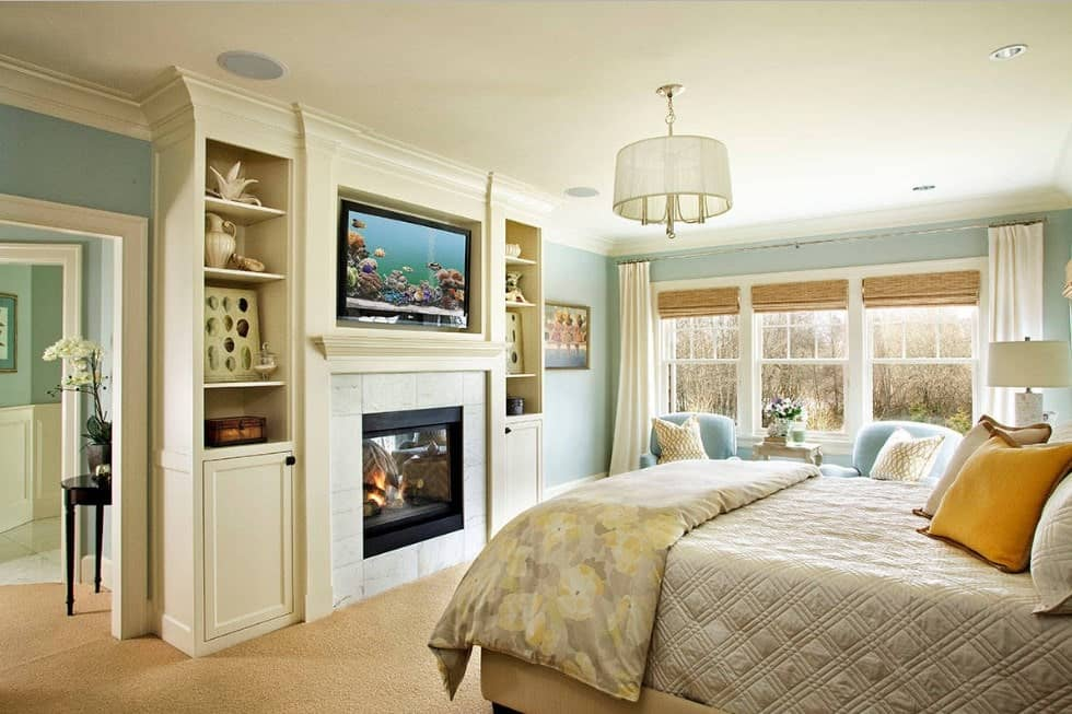 Bright master bedroom with light green walls and a white ceiling, along with beige carpet flooring. There's a sitting area near the windows, as well as a fireplace in front of the bed.
