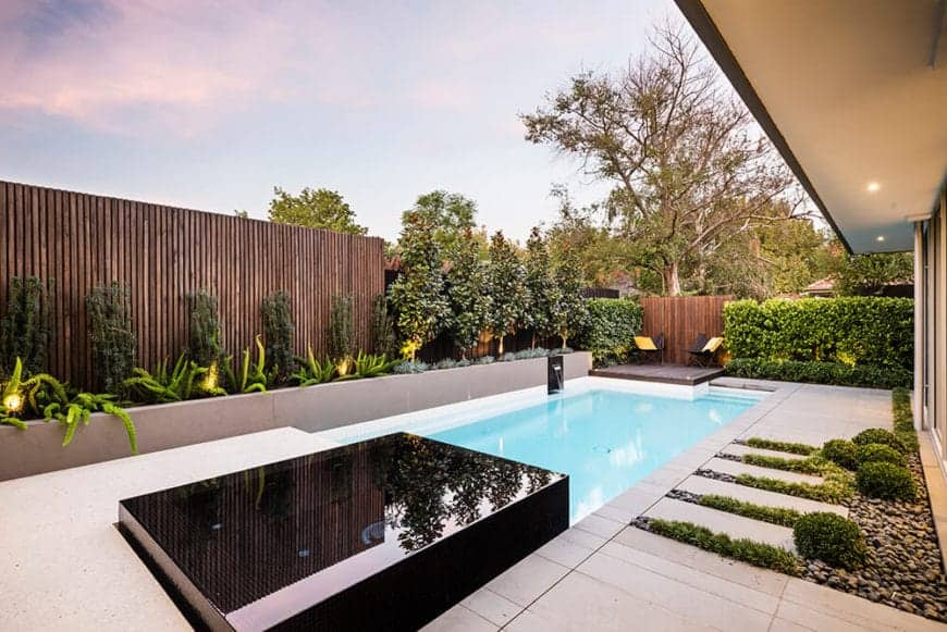 Minimalist pool with black mosaic tiles accent features wooden walls with a concrete planter box on a wooden and trimmed shrub wall.