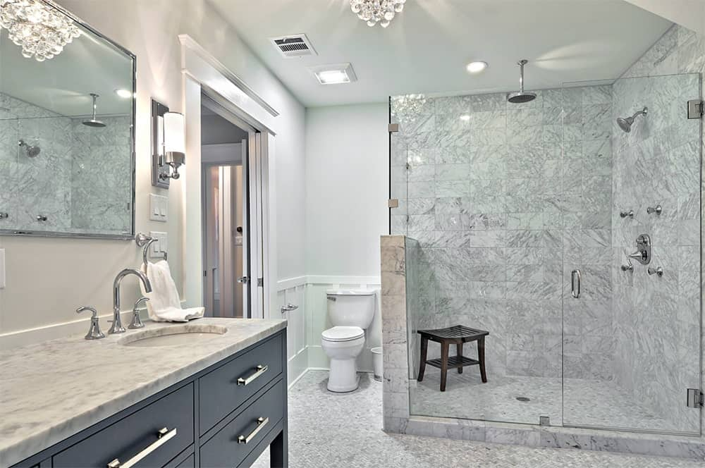 Traditional bathroom features a walk-in shower with wooden stool and marble tiles wall adjacent to a vanity sink with gray cabinets and marble countertop.