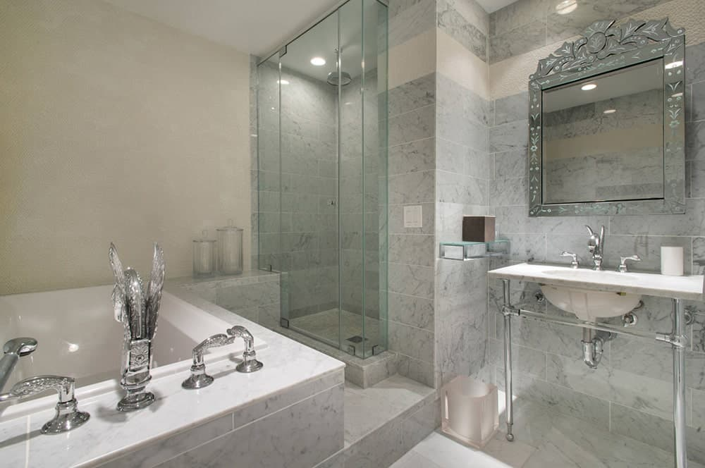 Contemporary bathroom features a bathtub with luxurious fixtures, walk-in shower next to it and a bathroom sink paired by a statement mirror.