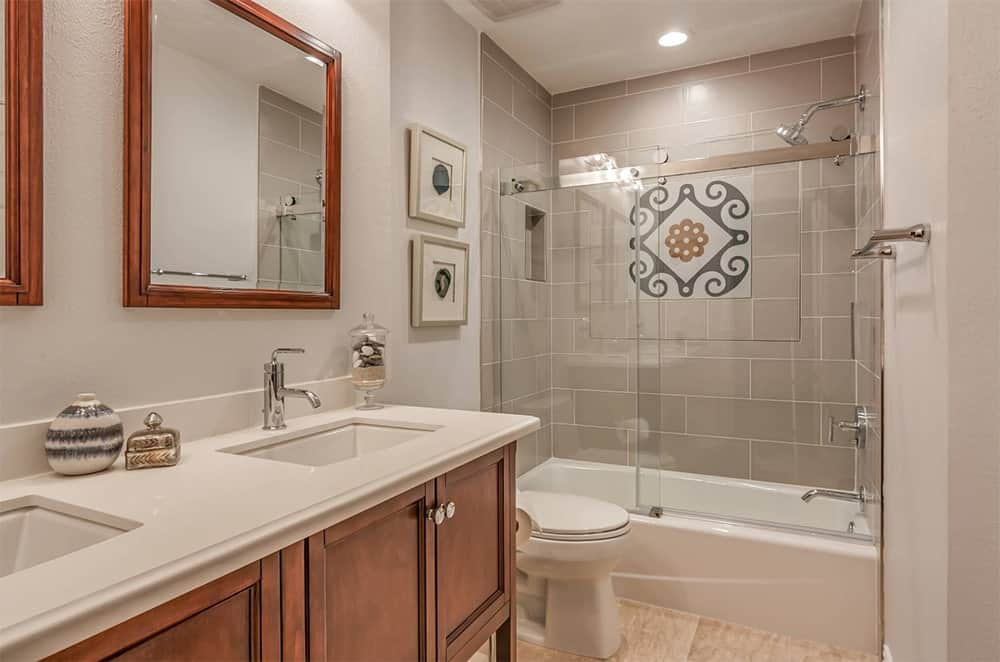 Mediterranean bathroom features a dual vanity sink with wooden cabinetry that matches the mirror and a walk-in shower tub combo accented by gray subway tiles wall.
