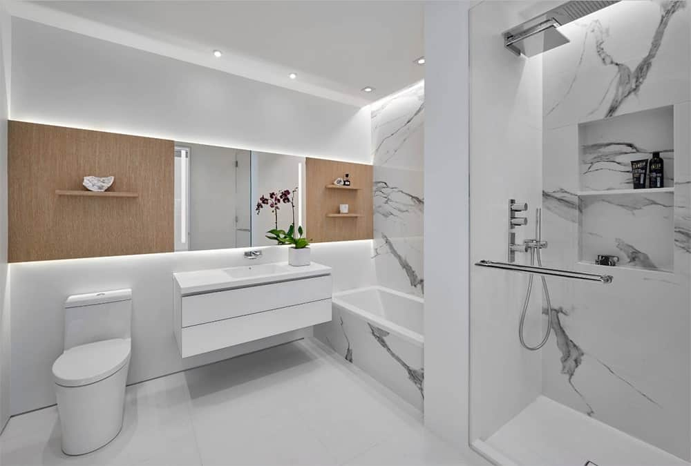 Clean, white bathroom accented by wooden walls with shelves and complemented by white marble tiles on the tub and shower area. It also includes a floating vanity sink with medicine cabinet mirror.