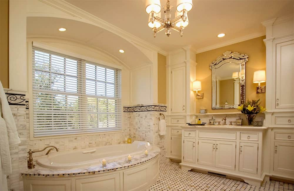 Yellow bathroom with subtle hints of gold features a corner bathtub beneath a window adjacent to a white vanity sink with gold mirror. It is lighted by wall sconces and a lovely chandelier.