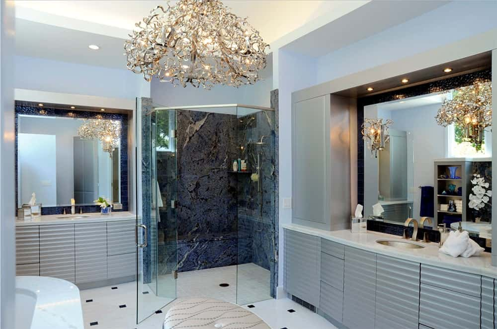Contemporary bathroom accented by unique chandeliers and walls sconces complementing the dark blue tiles wall on the walk-in shower.