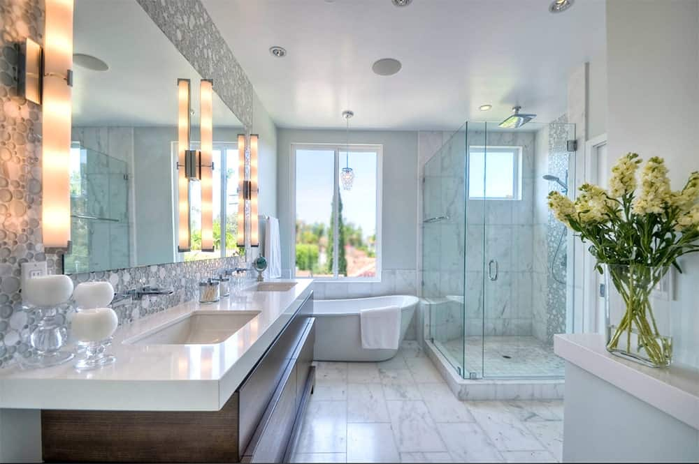 A white marble bathroom with a freestanding bathtub, walk-in shower and a dual sink vanity illuminated by vertical lights mounted on a glass wall tile and mosaic backsplash.