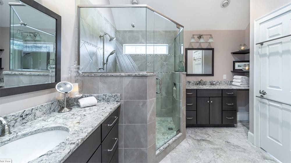 Sleek bathroom featuring a walk-in shower between two vanity sinks that are topped with gray marble and completed by dark wood cabinetry.