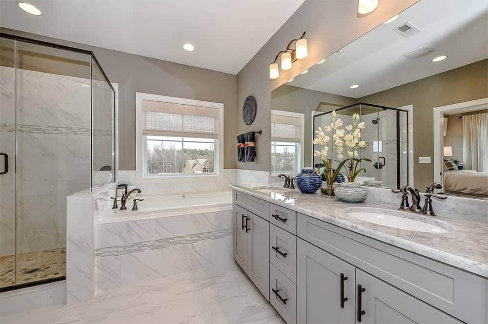 Transitional bathroom with a walk-in shower next to a marble corner tub and adjacent to the huge dual sink vanity with gray cabinetry and marble countertop.