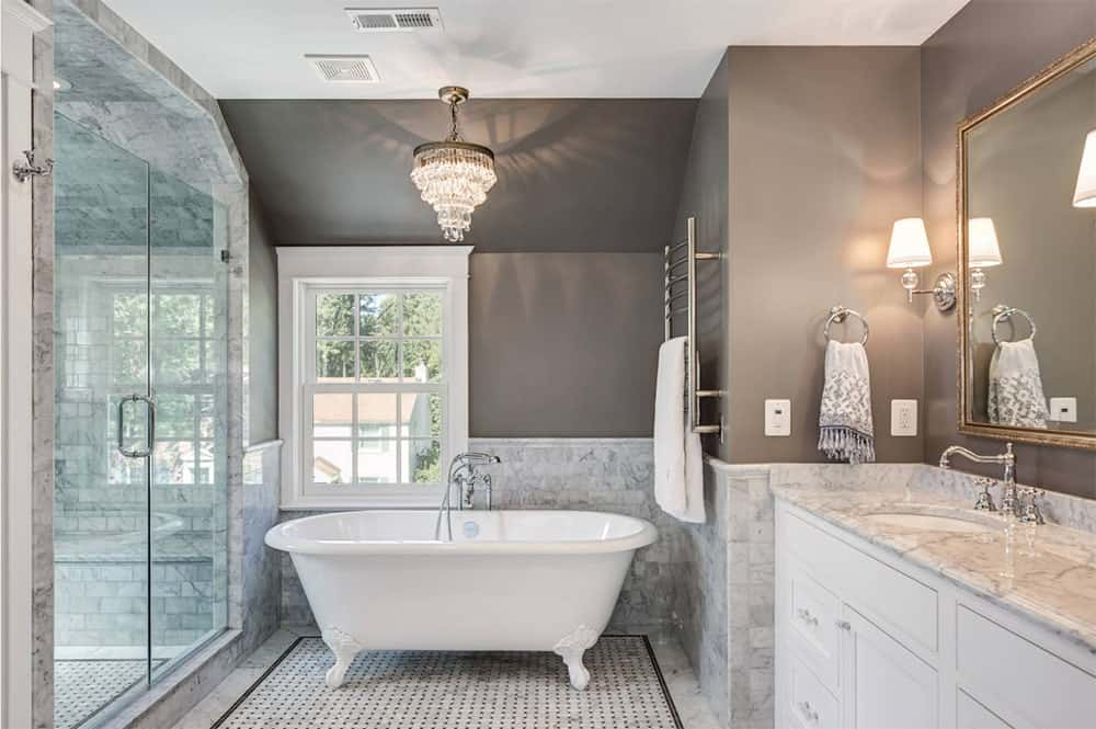 A fancy chandelier hung over a freestanding clawfoot bathtub in this lovely gray bathroom. It features marble tiles lower wall and floor, walk-in shower and a white wooden washstand.