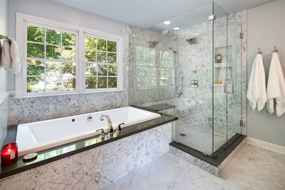 Gorgeous marble bathroom accented by black granite tiles with a bathtub beneath a framed window and walk-in shower next to it.