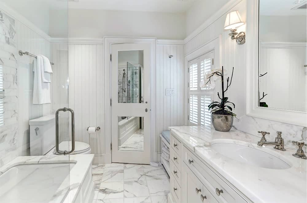 Clean white medium-sized primary bathroom with a bathtub facing the wooden vanity sink, both topped with white marble.