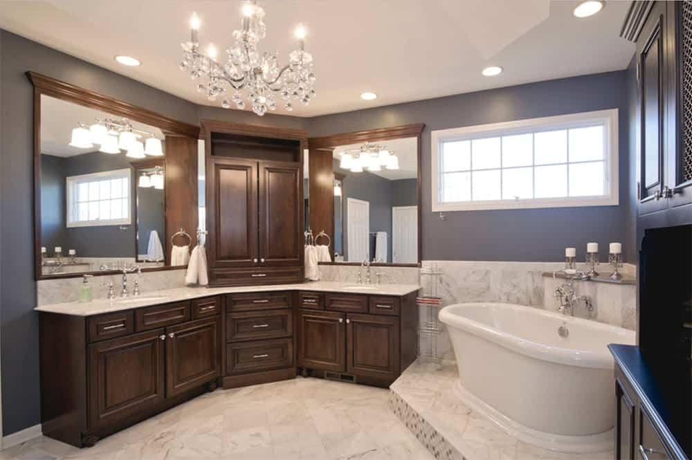 Traditional bathroom features a curved dual sink vanity with wooden cabinetry and a white marble countertop that matches the lower walls and flooring. It is lighted by wall sconces and a fancy chandelier.