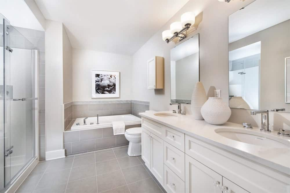 Gorgeous white bathroom accented by gray granite lower walls and floor tiles. It has a walk-in shower, a corner bathtub and a white dual sink vanity with frameless mirrors.