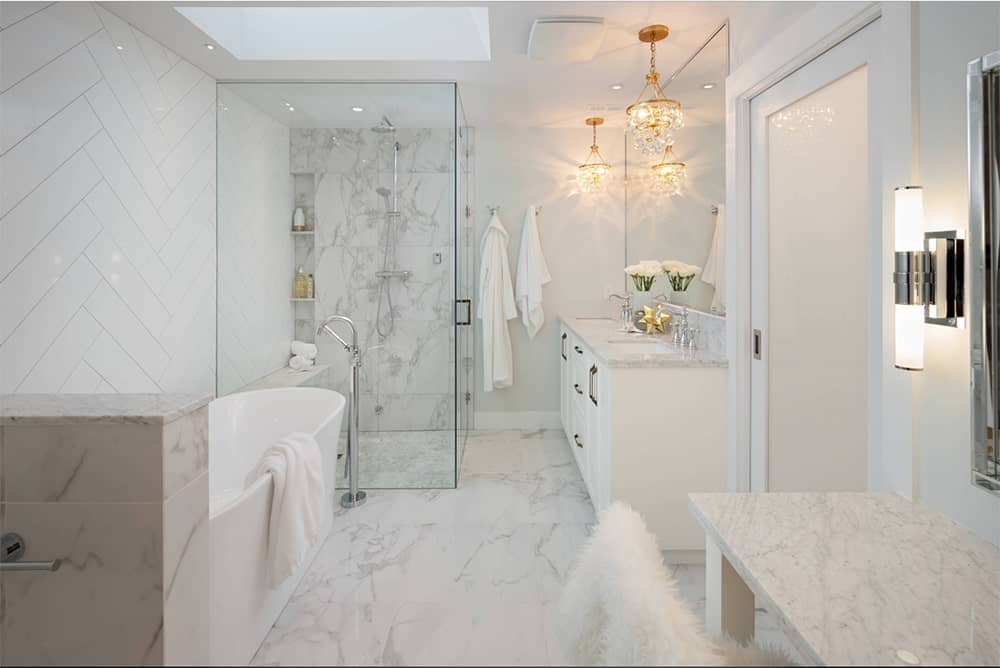 Glamorous bathroom features a bathtub, walk-in shower and a white dual sink vanity topped with gray marble and illuminated by fancy gold chandeliers.