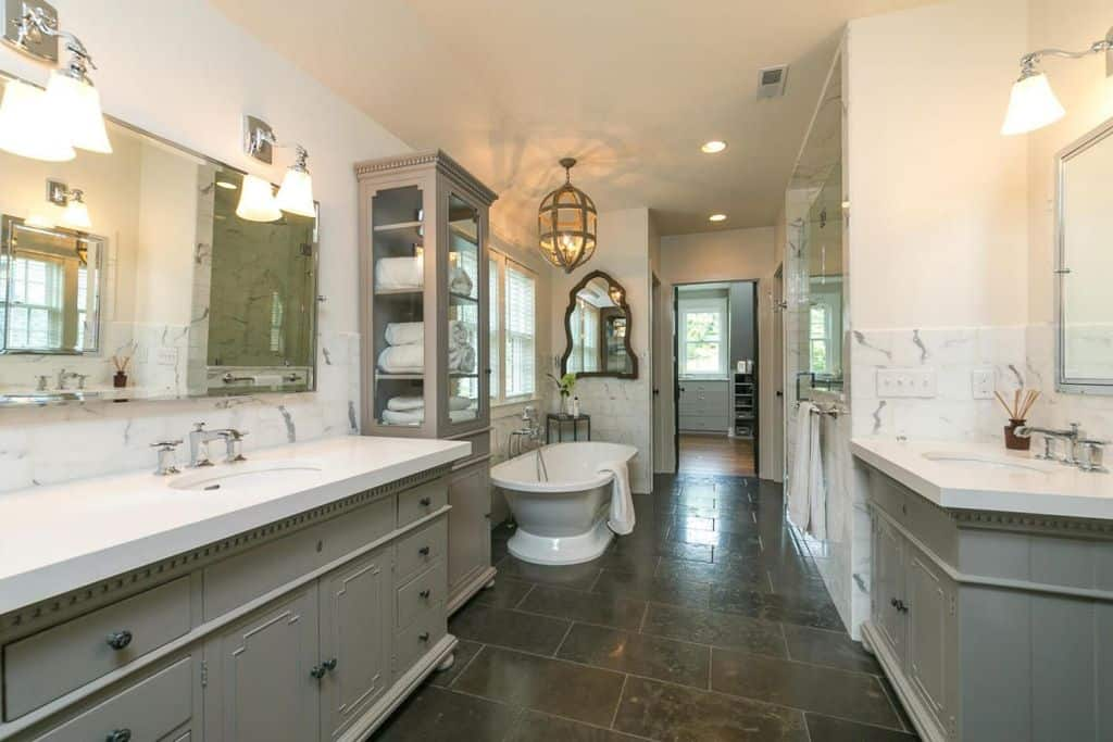 White bathroom accented by gray cabinets, marble countertops and black tiles flooring. It is lighted by a charming caged chandelier and wall sconces above vanity sinks.
