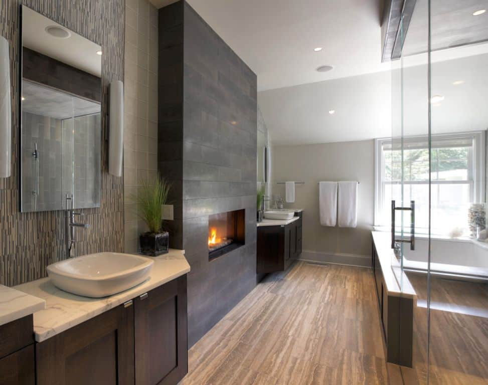 Galley bathroom with a walk-in shower that faces the vessel sink vanities where a fireplace mounted on a gray brick wall is centered.