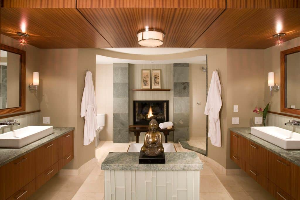 Antique bronze Buddha figurine provides a unique and enticing focal point along with the modern fireplace on this sophisticated symmetrical bathroom.