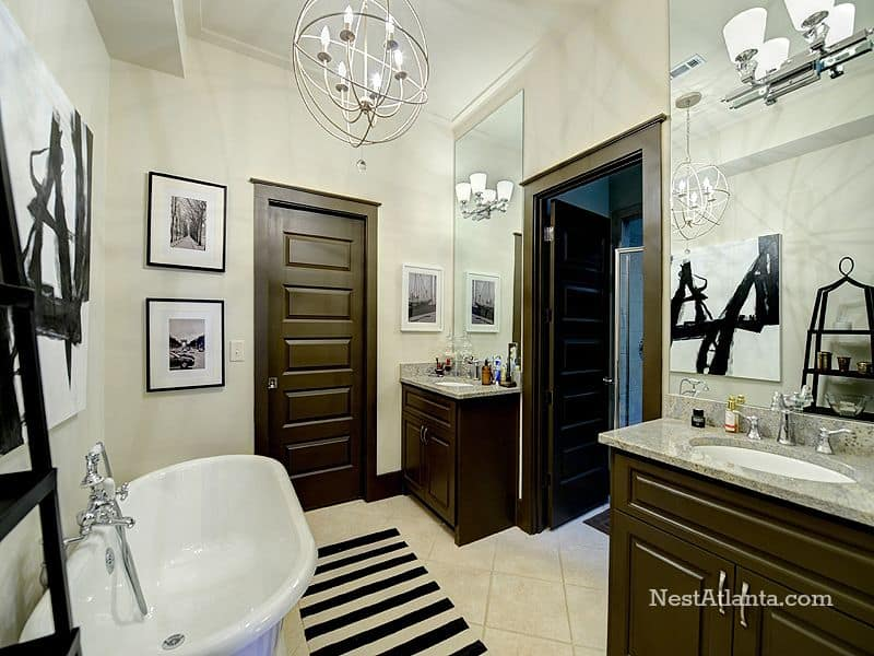 Fabulous black and white bathroom features an industrial spherical chandelier, a pair of washstands topped with gray marble, a freestanding bathtub and stripes rug complementing the wall canvas and frames.