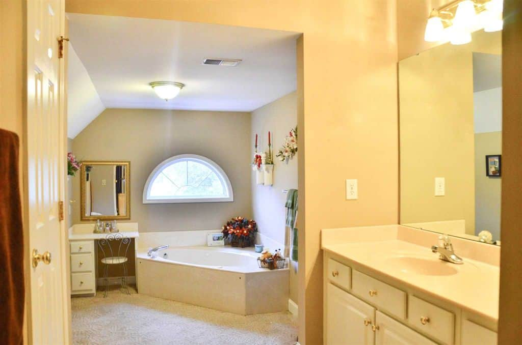 Warm, yellow bathroom featuring a corner bathtub beneath a semi-circular window and sits on a carpeted floor. Beside it is a small vanity table paired with gold mirror and metal chair.