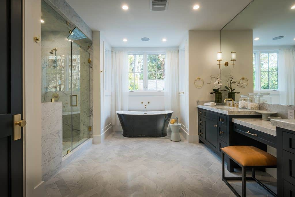 Elegant bathroom with a black bathtub complements black cabinets on the vanity sink that's topped with gray marble.