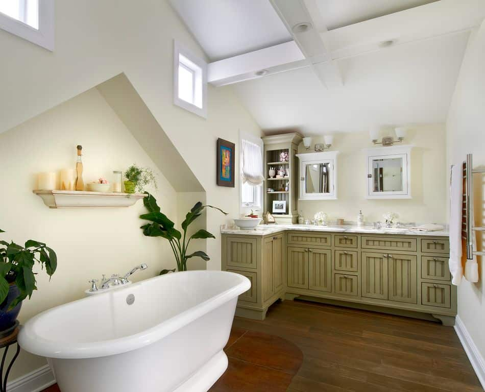 Medium-sized bathroom features an L-shaped vanity sink topped with gray marble and completed by wooden cabinets and a freestanding bathtub over a hardwood flooring.