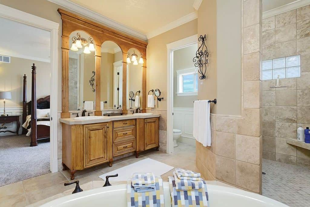 Elegant bathroom with tiled walls that matches the flooring and dual sink vanity with natural tone of wood cabinet lighted by fancy sconces.