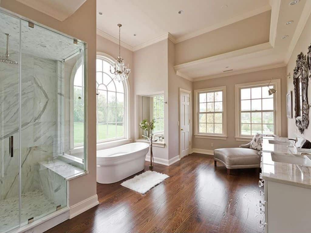 Cozy bathroom with dual sink vanity, a freestanding bathtub beneath an arched window, lighted by a gorgeous chandelier and a walk in shower next to it. A gray chaise lounge and hardwood flooring add warmth to the room.