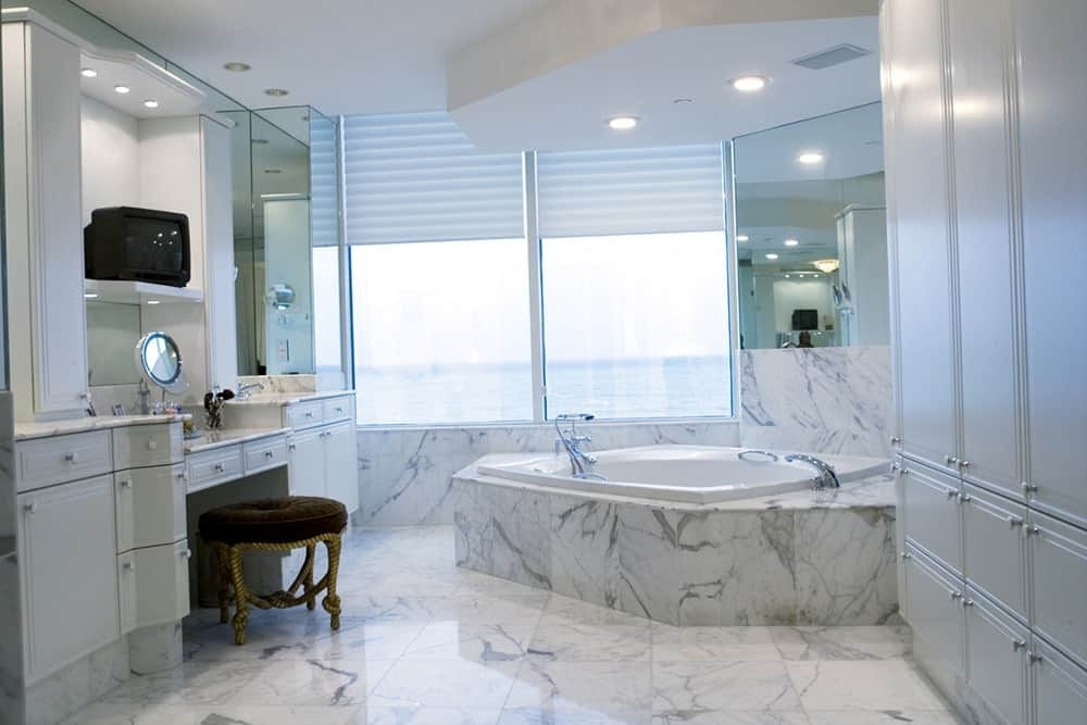 Gray marble covers the floor, walls and bathtub of this sleek medium-sized bathroom. It has vanity sink with a brown cushioned stool that faces a huge gray cabinet and windows with a spectacular view of the beach.
