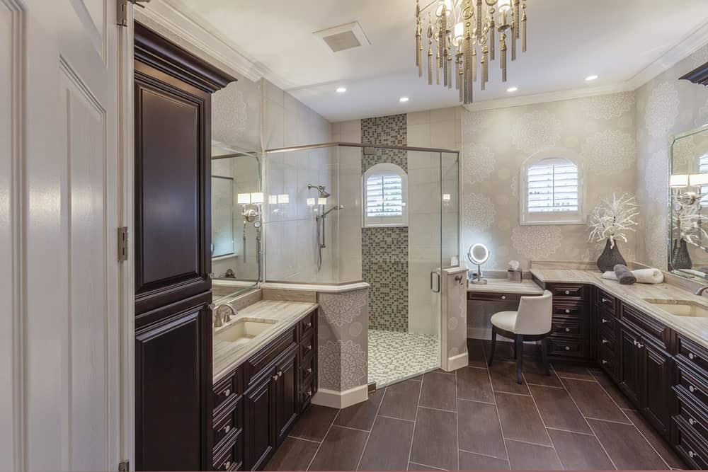 A walk-in shower accented by mosaic tiles is surrounded by dark wood washstands with gray marble countertop on this chic bathroom. It features a lovely chandelier that hung over a hardwood floor.
