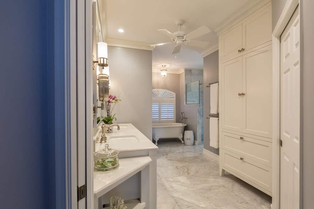 White ceiling fan hung over this white and gray bathroom which boasts a huge white built-in cabinet facing the dual sink vanity and a freestanding clawfoot bathtub.