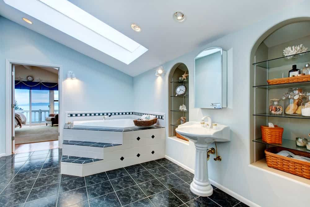 Fresh medium-sized master bathroom features white sloped ceiling with skylight, black tiles flooring and a frameless medicine cabinet mirror hung over a white ceramic pedestal wash bin.