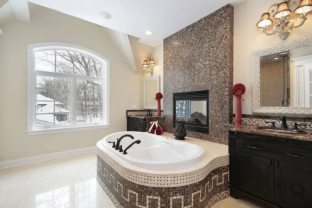 Glamorous bathroom features a bathtub fixed to a mosaic accent tile wall. It is centered in the middle of black wood washstands with marble countertops and white mirrors illuminated by fancy wall lights.