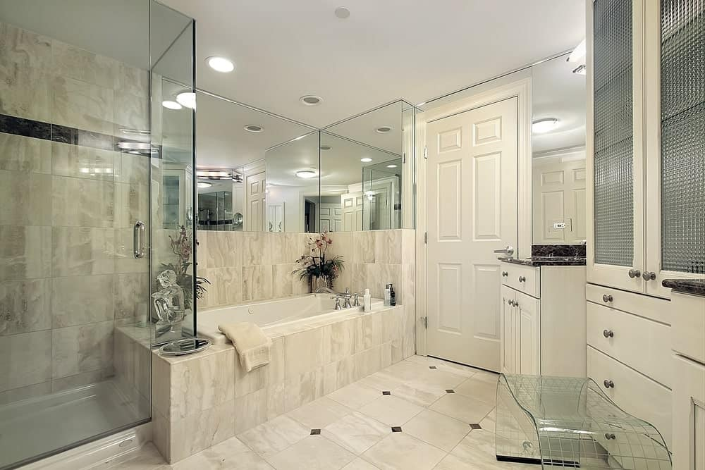 White medium sized bathroom features a bathtub and glass shower enclosure along with marble tile walls and floor. It has a frosted glass front linen cabinet and a white wooden washstand with black marble countertop next to it.