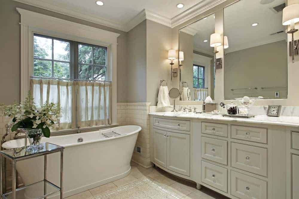 Medium-sized master bathroom with white crown moldings and walls painted by silver gray color. It has a bathtub and a huge vanity with two mirrors lighted by wall sconces.
