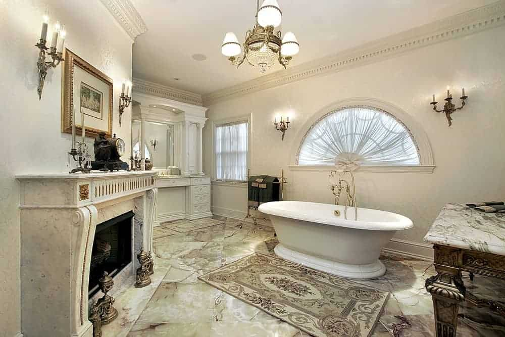 Luxurious bathroom features a freestanding bathtub paired by a vintage rug that complements the elegant marble floor and a traditional style fireplace. It is illuminated by a fancy chandelier and candle wall sconces.