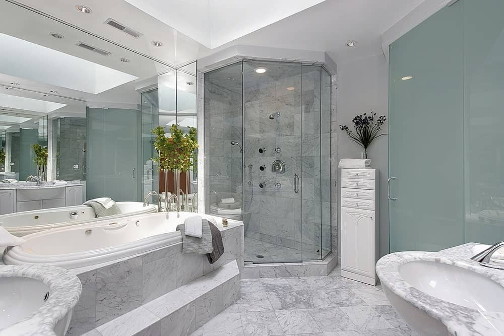 Elegant bathroom with marble covering the floor, sink, bathtub and wall tiles inside the glass shower enclosure. It features a huge mirror beside the bathtub, glass door and a small white storage cabinet.