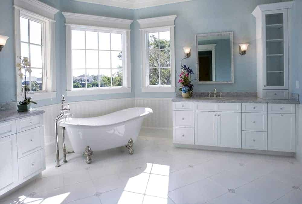 Lovely white and blue bathroom with a freestanding clawfoot bathtub in the middle of white wood washstands topped with gray marble.