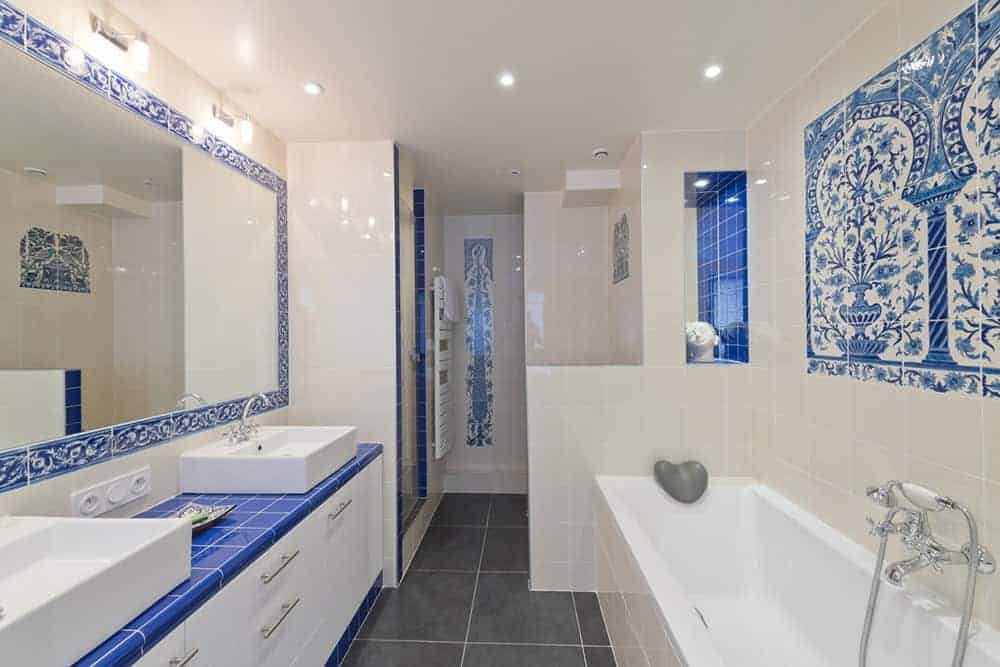 White tiled bathroom accented by blue plain and patterned tiles over the walls, countertop and mirror's border frame. It has a huge vanity with double vessel sinks completed by white cabinets and chrome pulls.